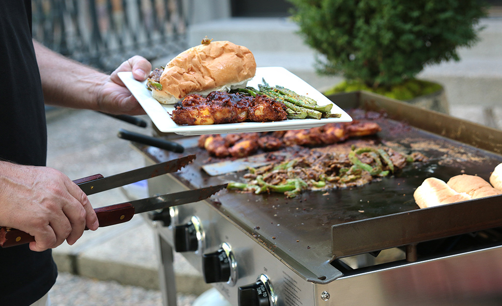 A person cooks meat and vegetables on a flat top gas grill.