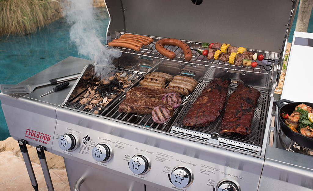 Ribs, sausage, skewers and other foods cook on an infrared gas grill.