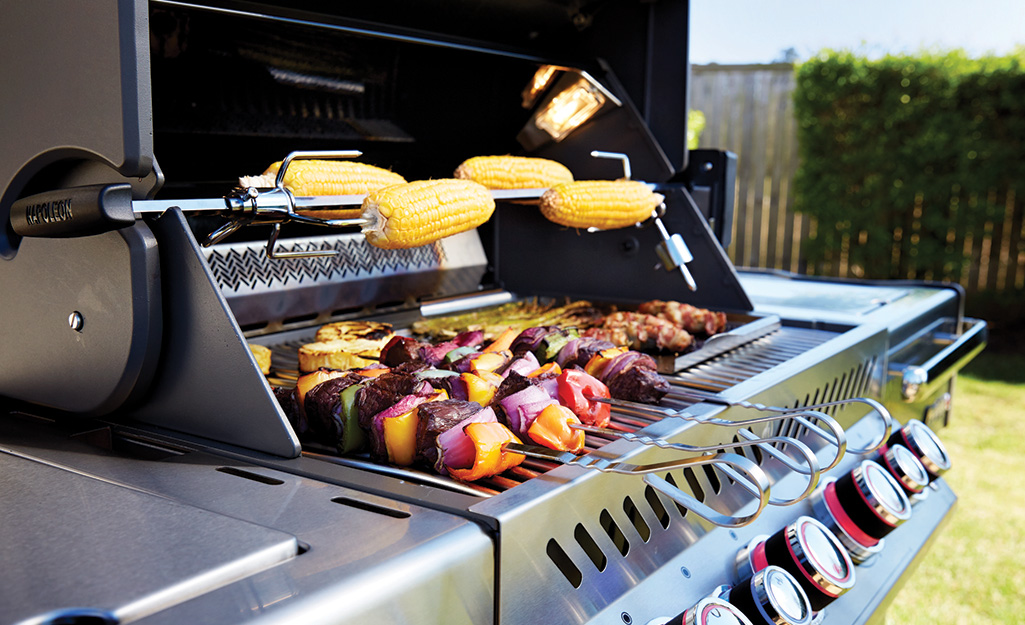 Corn on the cob turns on a rotisserie rotation accessory on a gas grill.