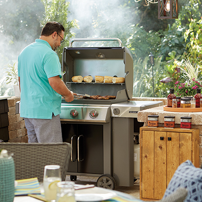 A person cooks on a propane gas grill on a patio.