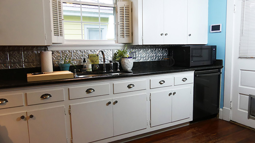 A microwave sitting on a countertop above a black stainless steel dishwasher.