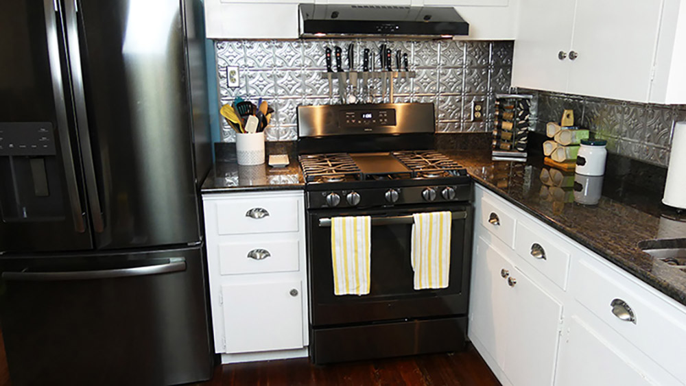 The corner of a kitchen with a GE black stainless steel gas range and under the cabinet range hood.