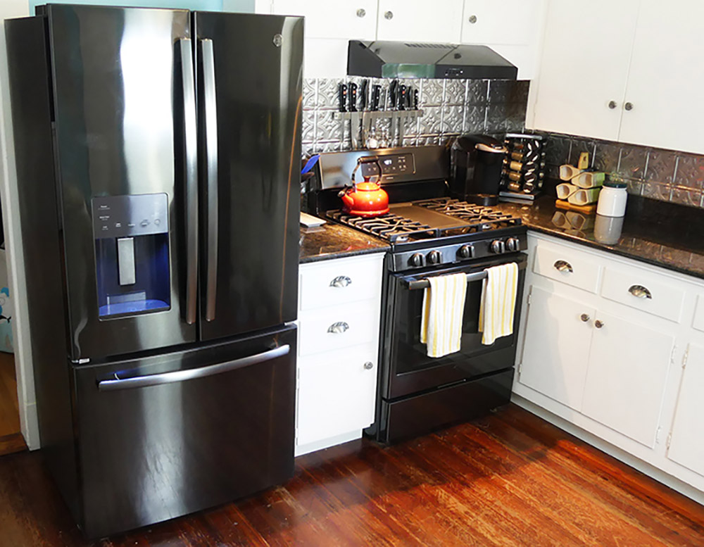 A GE black stainless steel counter depth French door refrigerator.