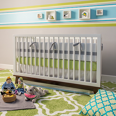 A white crib in a nursery with green and blue decor.