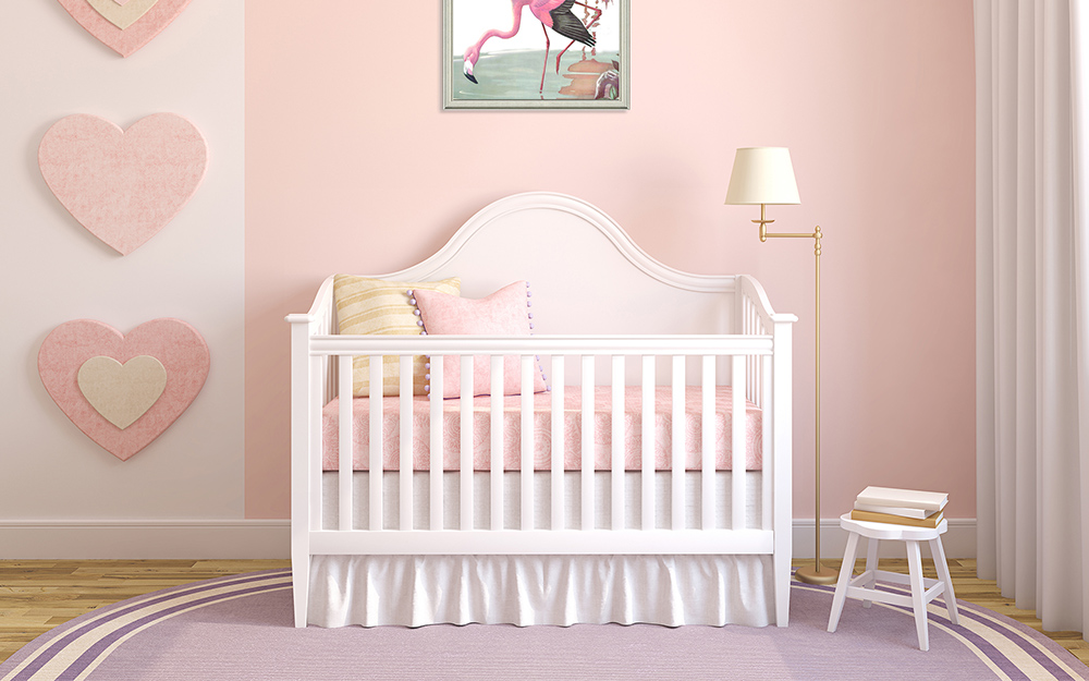 A girl's nursery with pink and white walls and a white crib.