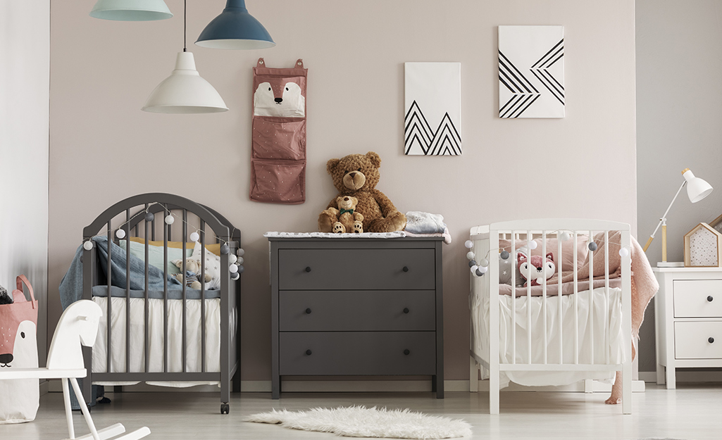 A nursery for twin girls with gray walls, a peach-colored crib and a wooden initial hanging on one wall.