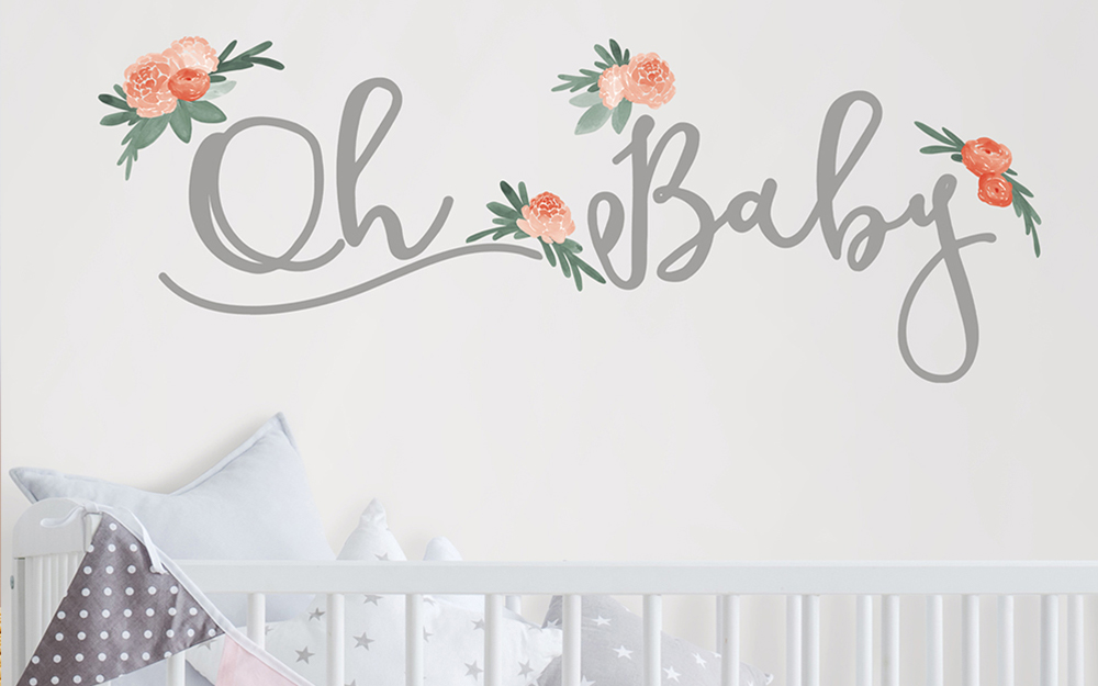 """A girl's nursery with a white crib and walls and an """"Oh Baby"""" decal on one wall."""