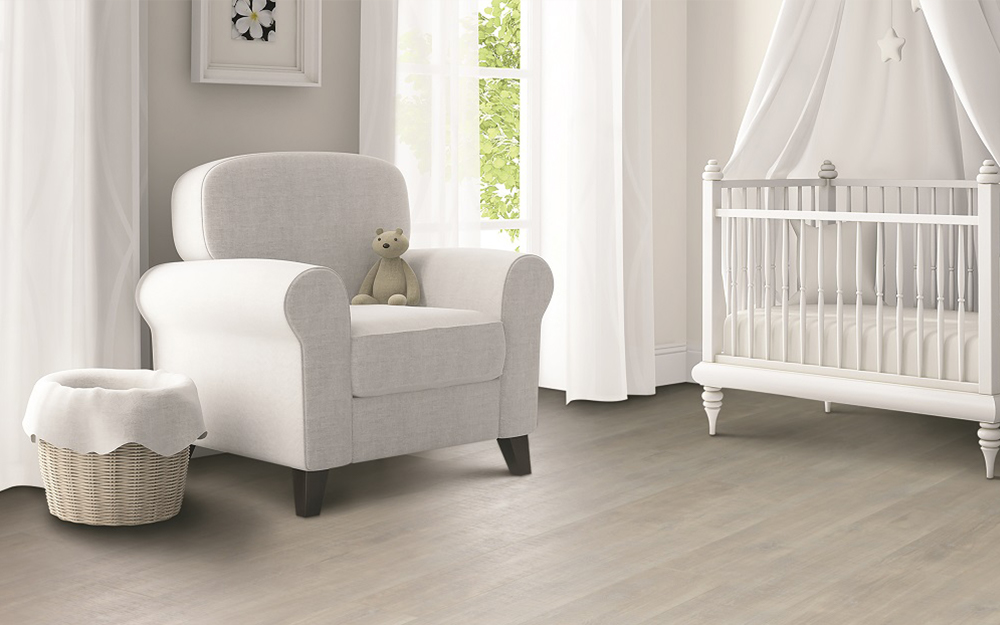 A girl's nursery with a white chair, crib and crib bedding and a light wood floor.