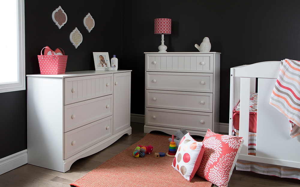 A girl's nursery with dark walls, a white dresser, changing table and crib and pink accents in a lampshade, basket, blanket and pillows.