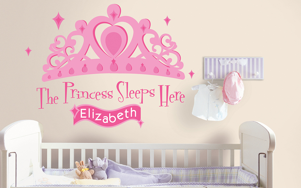 A white and pink girl's nursery with a princess decal over the crib.
