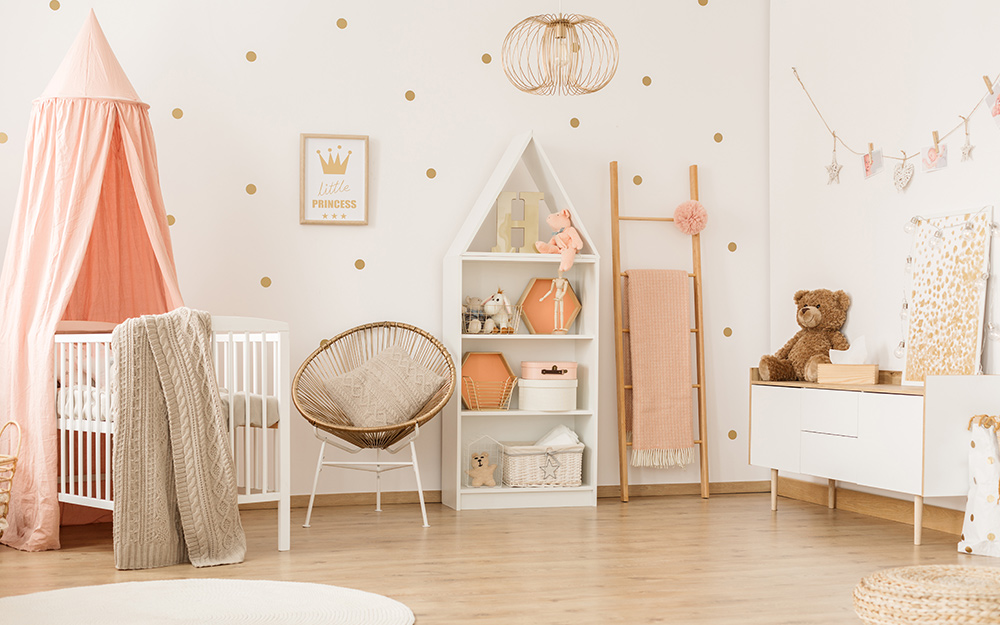 A girl's nursery with white walls with gold polka dots and peach-colored accents in a crib canopy, accessories and blankets.