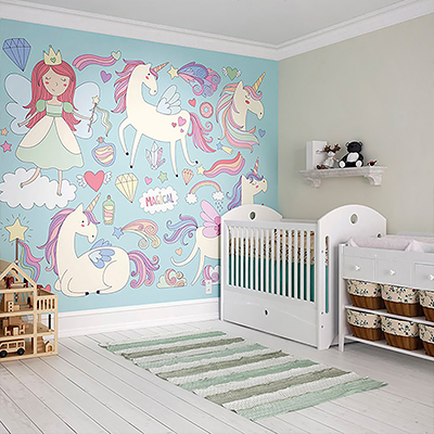 A girl's nursery with a unicorn, fairy and other designs on one wall.
