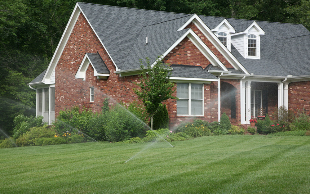 Brick home with sprinklers running on a grass lawn.