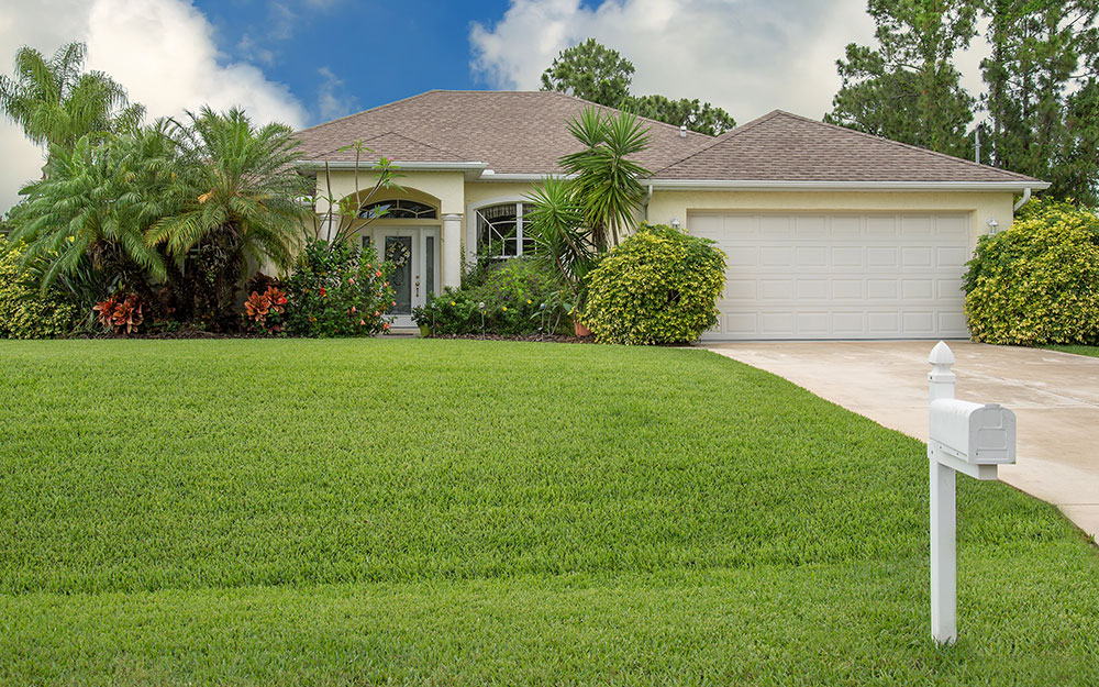 Home and driveway with a green grass lawn.