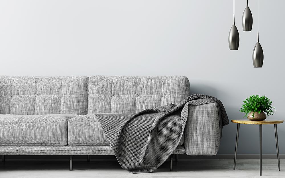 ghế sofa màu xám với một chiếc chăn màu xám và ngon lành trong phòng khách