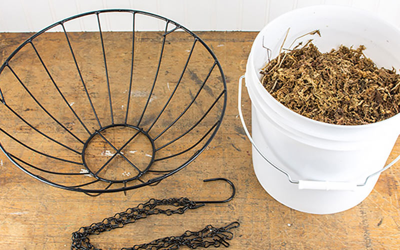 Metal hanging basket and bucket of sphagnum moss