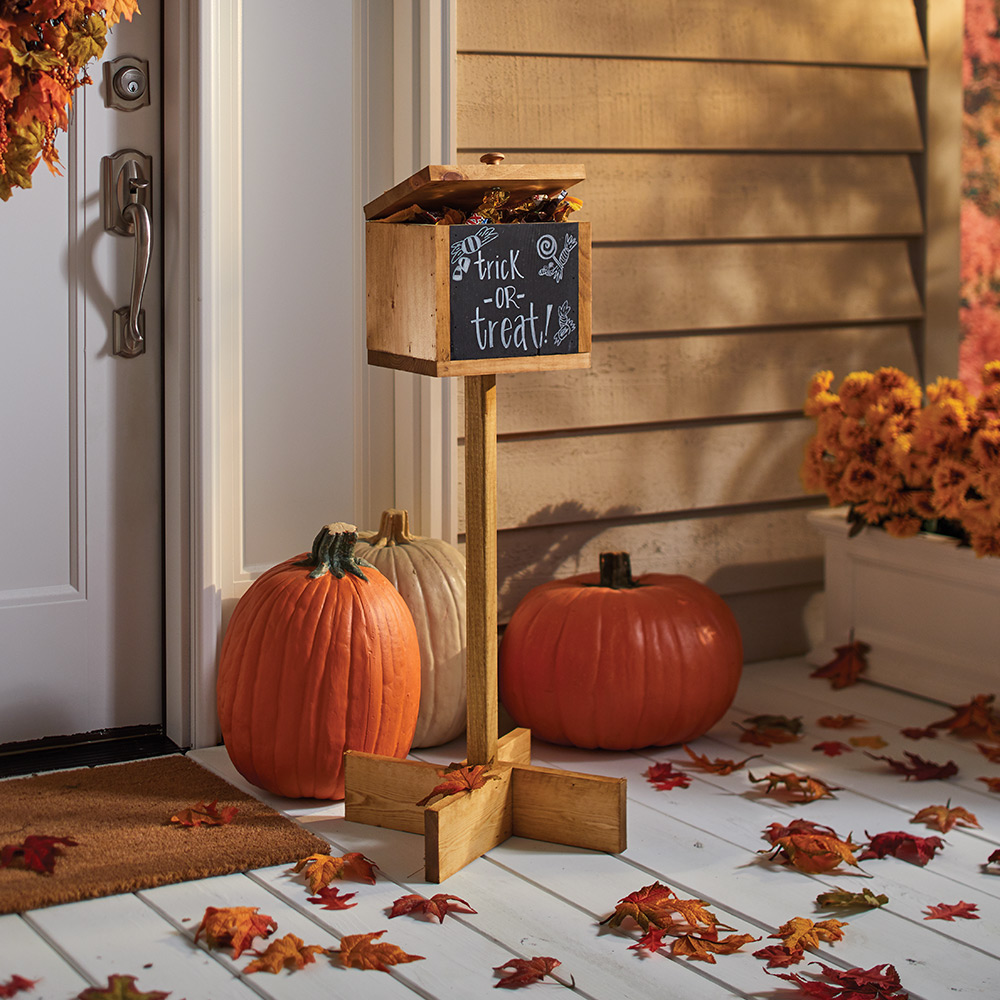 A finished halloween candy holder sits on a porch with pumpkins.