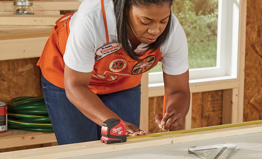 A woman measures her boards with measuring tape.