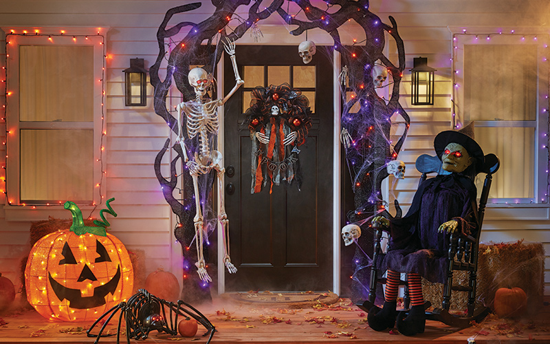 a halloween front porch display with lights, pumpkins and other props