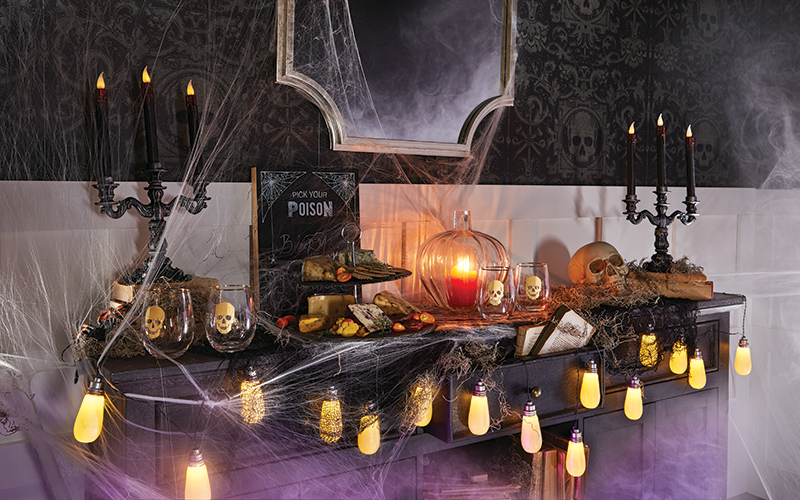 a halloween side table display with string lights, candelabras and other trinkets