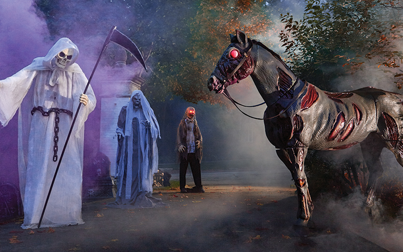 a halloween yard display with a grim reaper and zombie horse inflatables