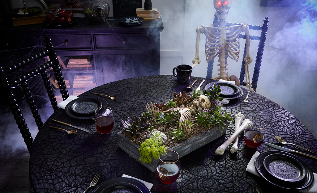 A table with a halloween coffin centerpiece.