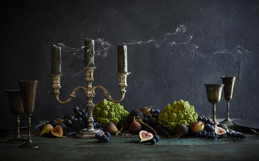 A table with black candles and fruit on top.