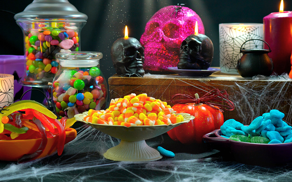 A table decorated for halloween with a candy centerpiece.