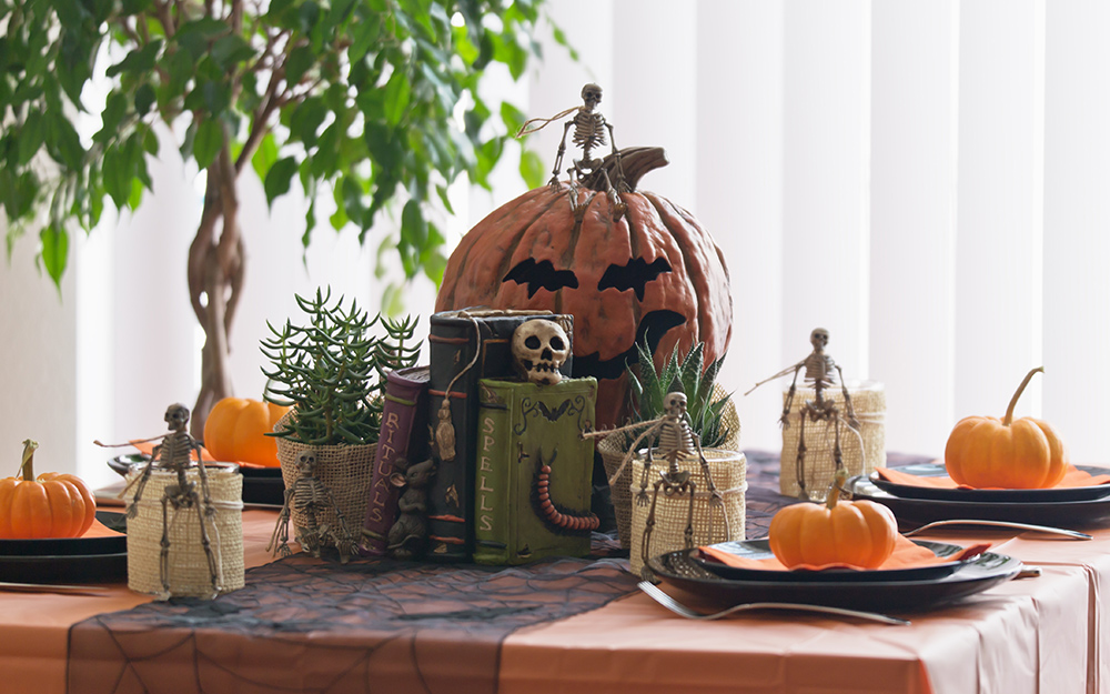 A table decorated for halloween with squash and skeletons.