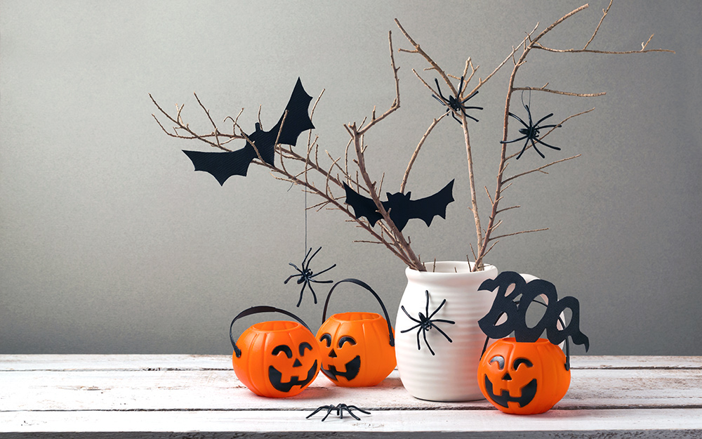 A halloween centerpiece made with a jar, twigs and bats.