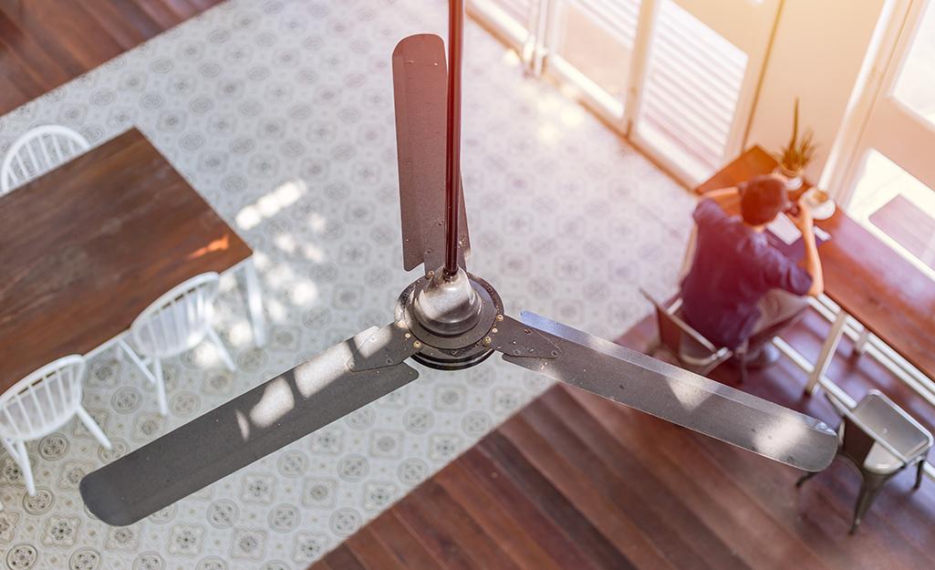 Góc nhìn từ trên xuống của một chiếc quạt trần và một người đàn ông đang ngồi trên bàn.