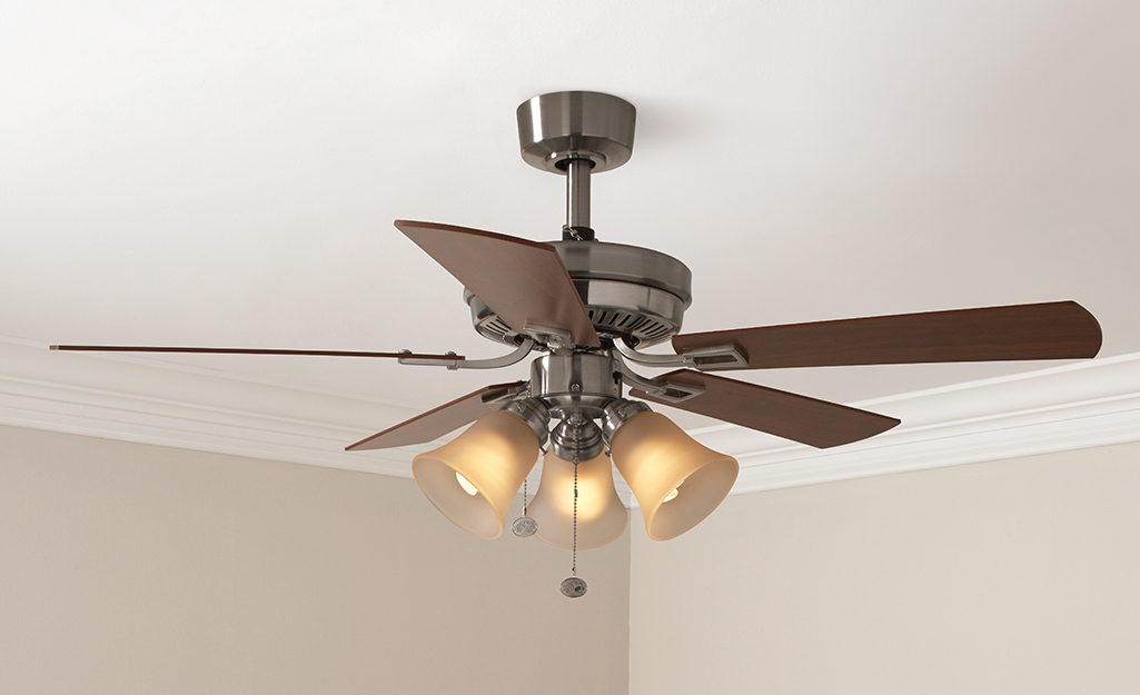 A brown Hampton Bay ceiling fan with three down lights.