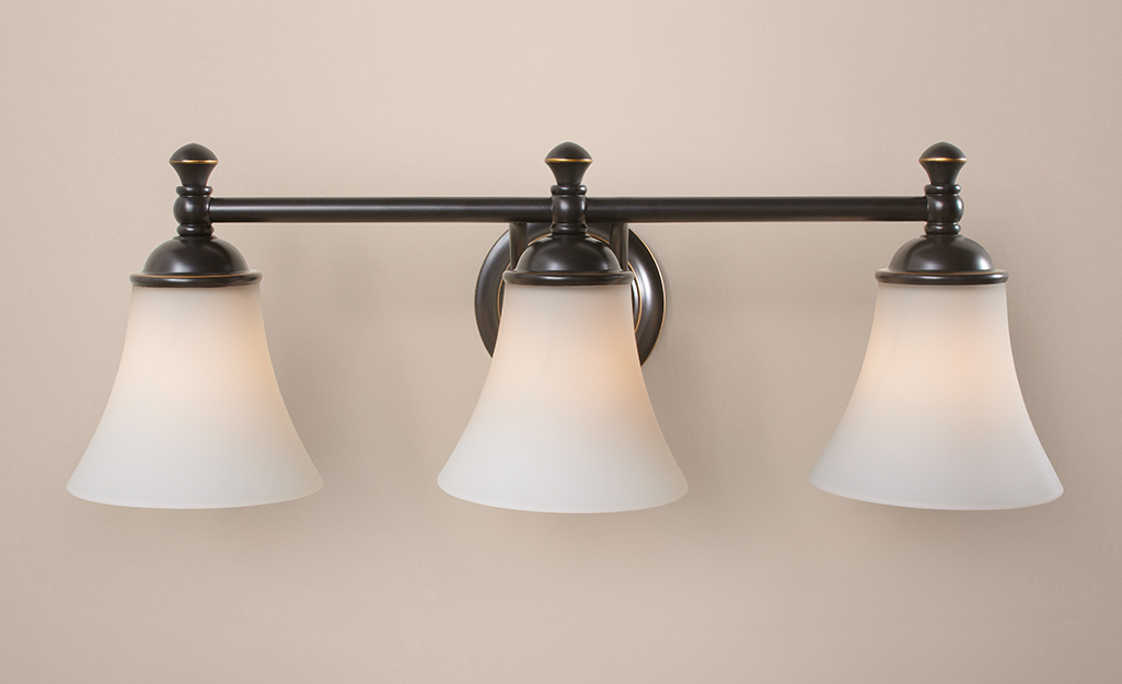 A Hampton Bay wall sconce with three down lights with frosted shades.