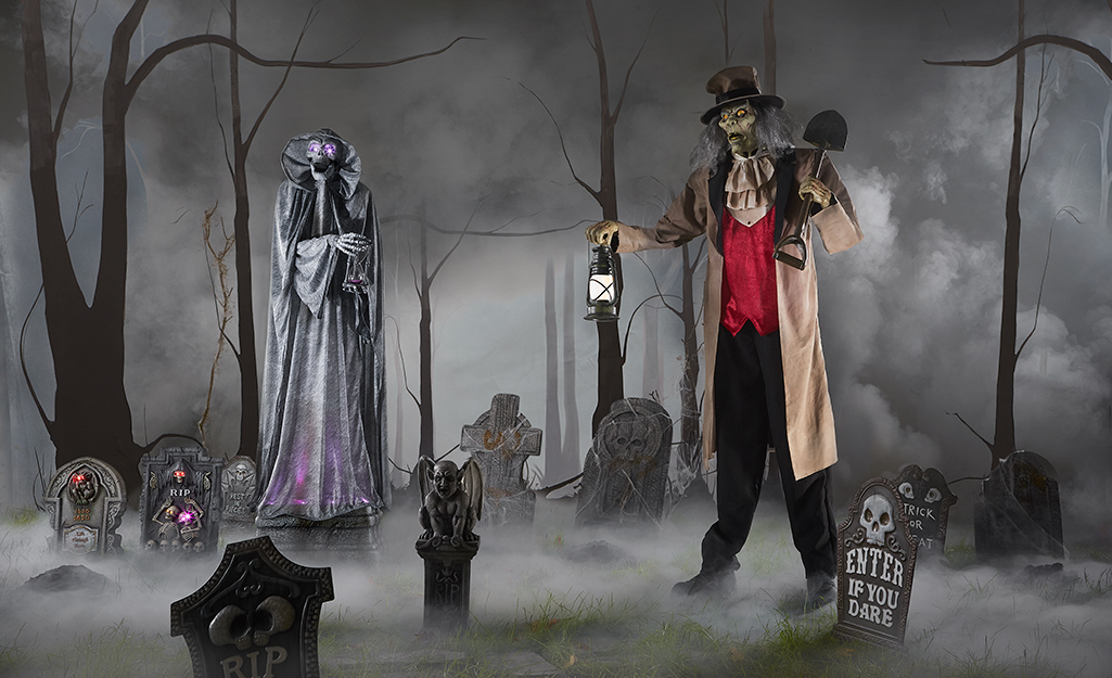 A spooky yard display with skeletons and smoke.