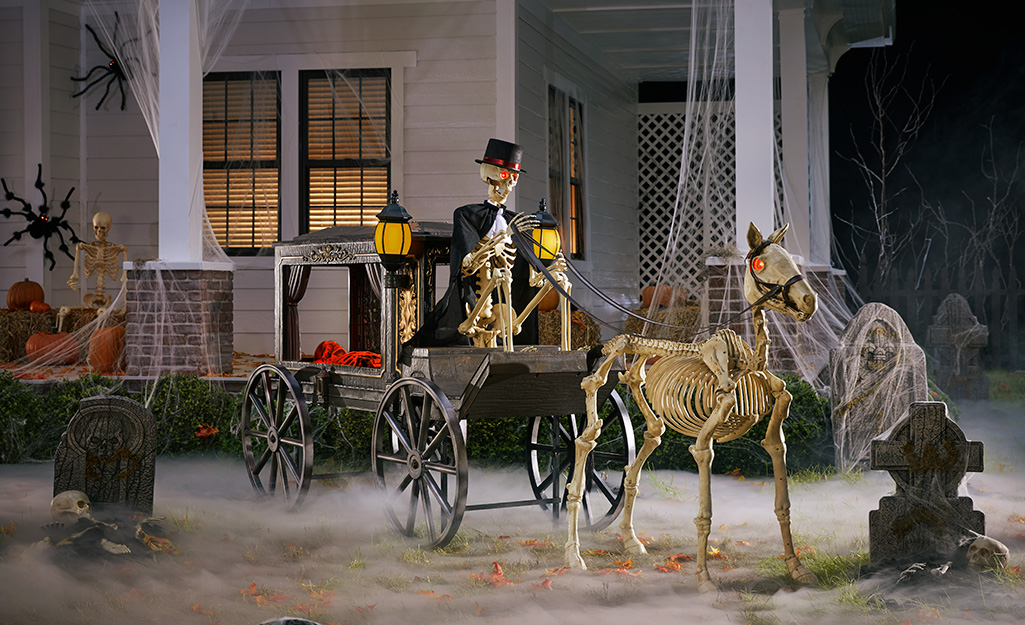 A skeleton driving a haunted carriage on a lawn.