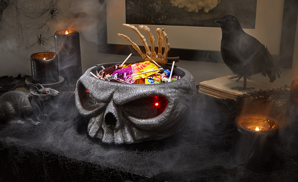 A candy bowl with glowing eyes holds candy.