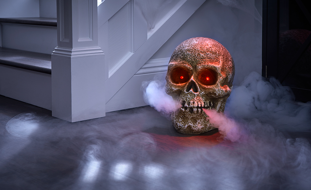 A skeleton head with glowing eyes and smoke escaping his mouth and eyes sits on a floor.