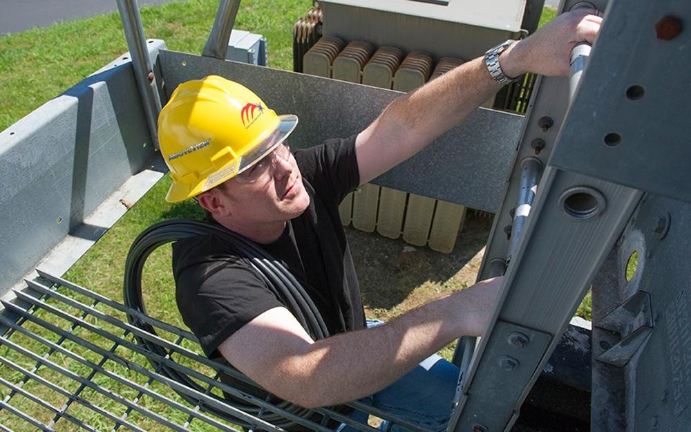 a man climbing a tall ladder wearing a yellow hard hat