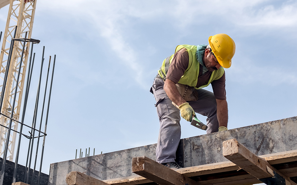 a man working on top of a building wearing a hard hat
