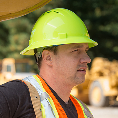 a man wearing a yellow hard hat on a construction site