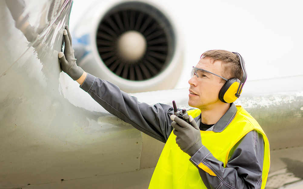 An airline worker wearing ear muffs for hearing protection.