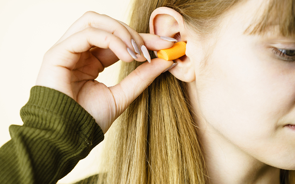 A woman inserting a disposable ear plug for hearing protection.