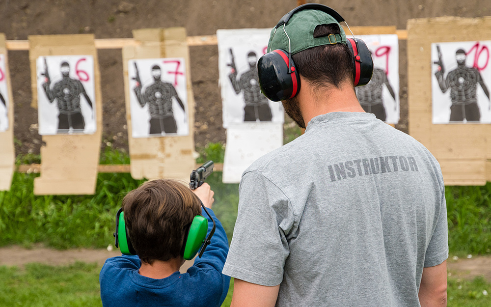 Two people wearing ear muff hearing protection at a shooting range.