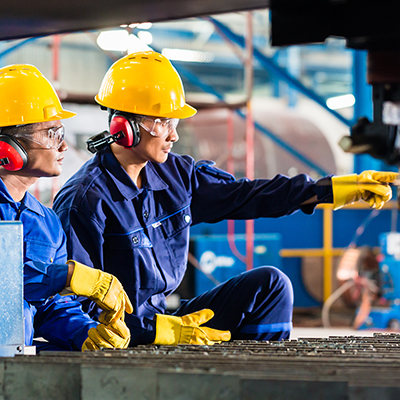 Two factory workers wearing hearing protection.
