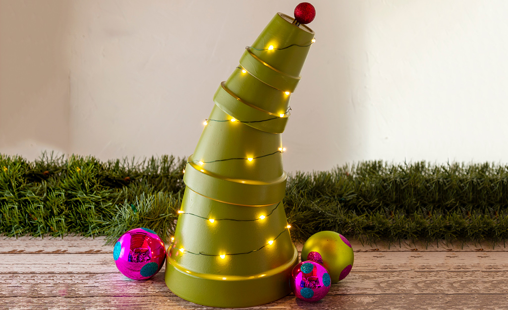 Four terra cotta pots painted green are stacked in a leaning tower to resemble a Christmas tree.