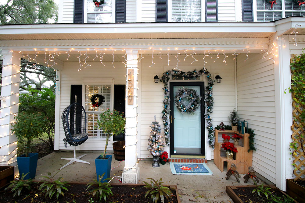 A front porch is decorated for the holidays with porch Christmas trees, garland, and a wreath.