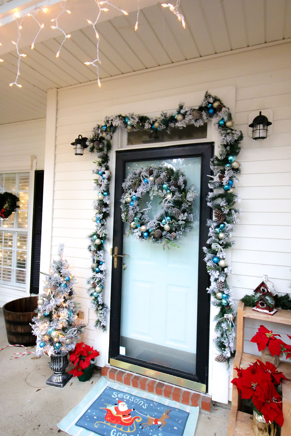 A front door with a flocked holiday wreath decorated with blue and gold ornaments.