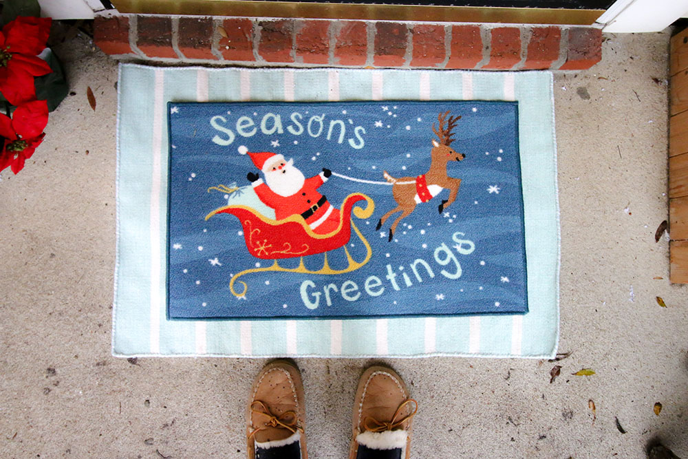 A seasons greetings doormat sits on top of a blue and white rug.