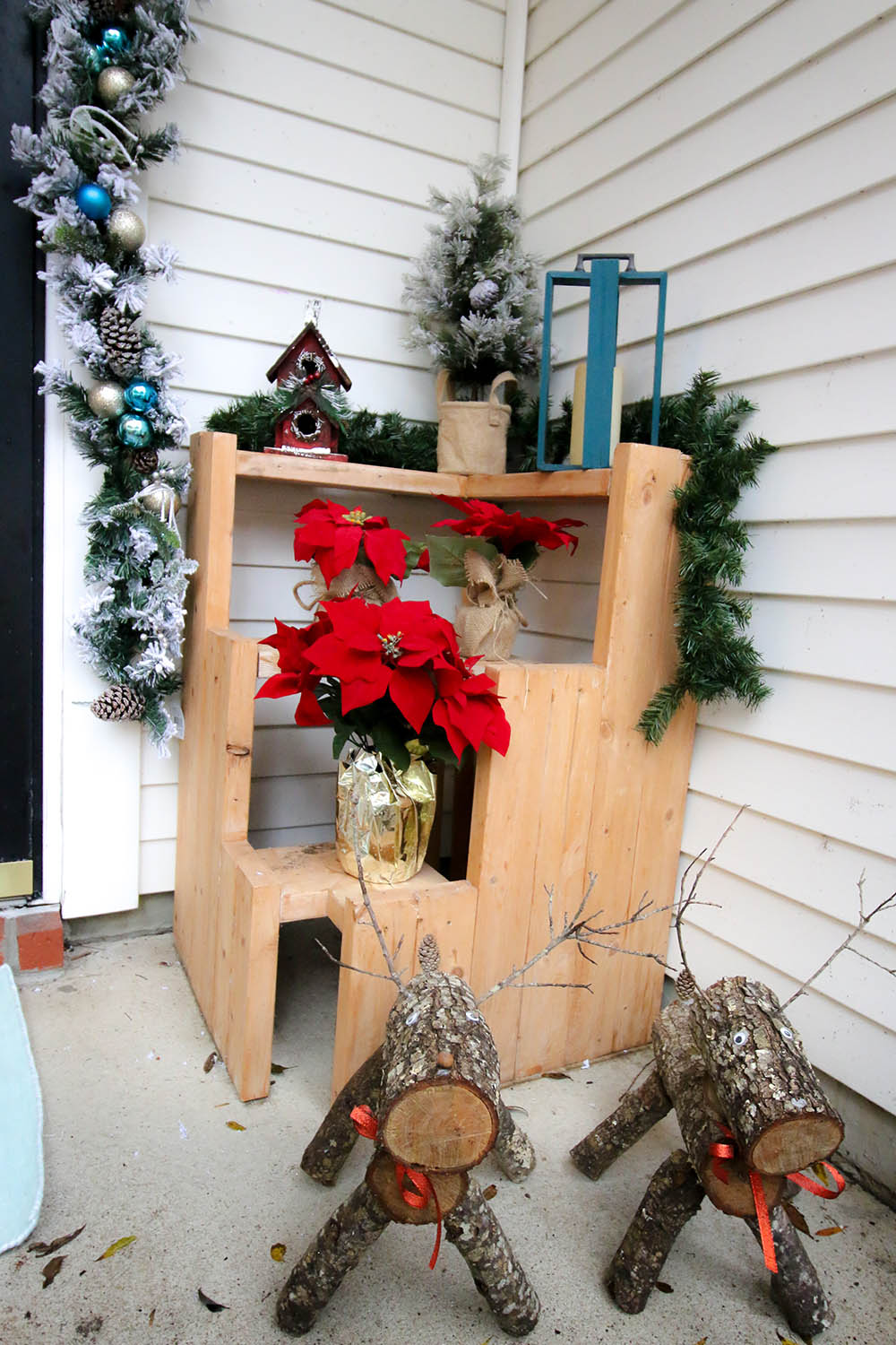 Two DIY wood slice reindeer standing in front of a three-tiered plant stand decorated with garland and poinsettias.