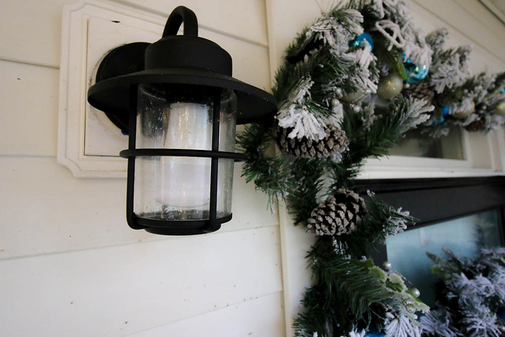 A coastal wall mounted lantern next to a front door surrounded by flocked garland.